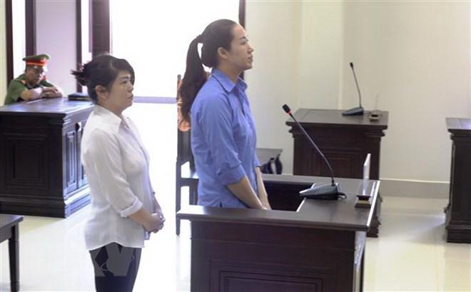 Hai bị cáo nghe tòa tuyên án. (Ảnh: Lê Đức Hoảnh/TTXVN)