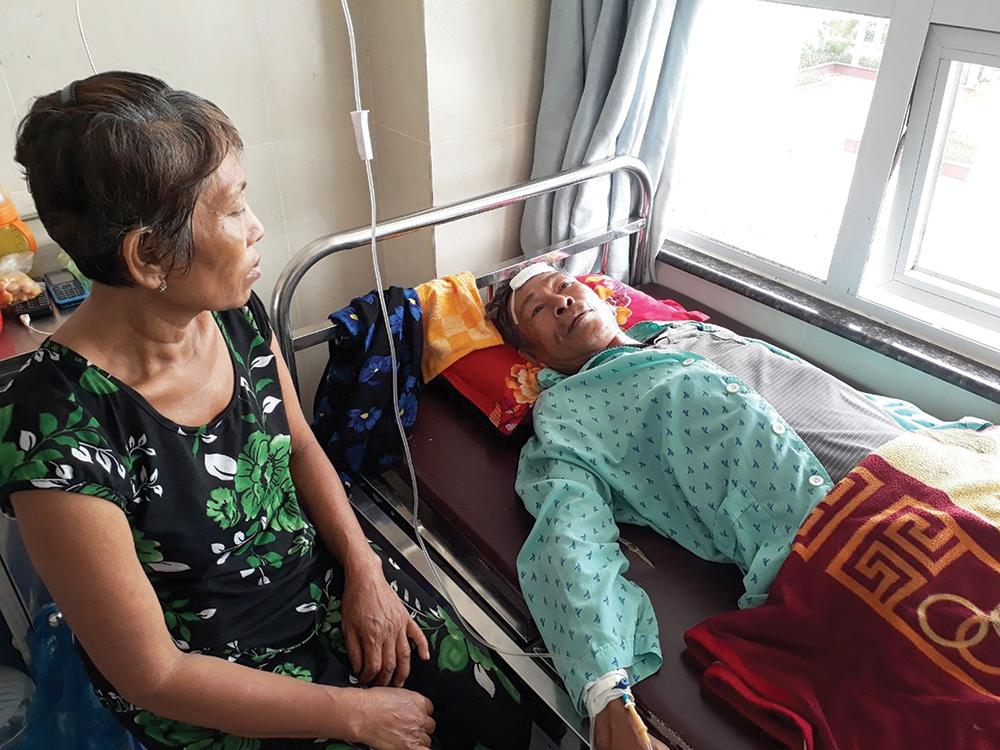 Bà Phỉ đang chăm sóc ông Hùng tại bệnh viện