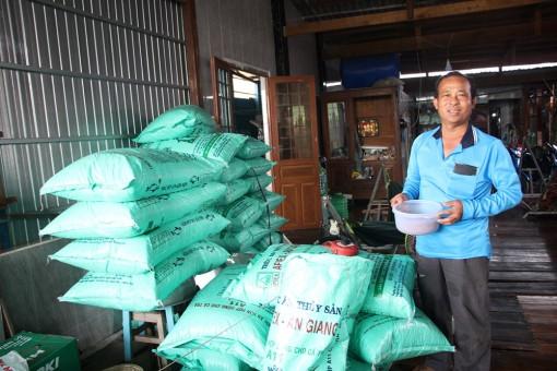 Một nông dân ở Chợ Mới dụ nuôi hàng ngàn cá tra sông tự nhiên trước bến sông nhà để ngắm